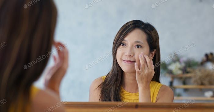 Woman use finger touch on her face in beauty make up studio