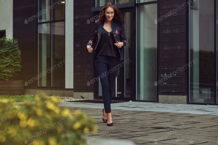 Smiling sensual brunette woman in stylish fashion clothes walking on the street.