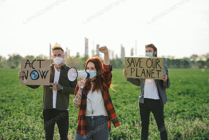 Group of young activists with placards standing outdoors by oil refinery, protesting