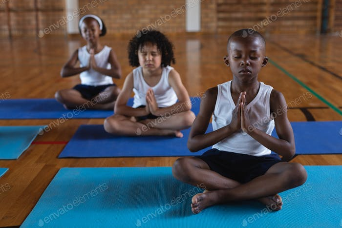 Front view of schoolkids doing yoga and meditating on a yoga mat in school