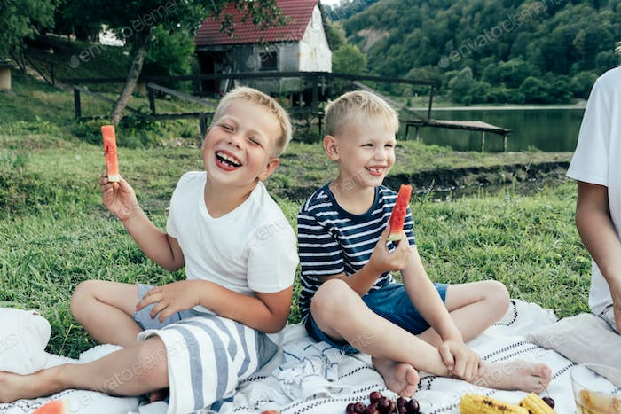 Two preteen boys laugh with joy at the picnic. Children hold pieces of watermelon