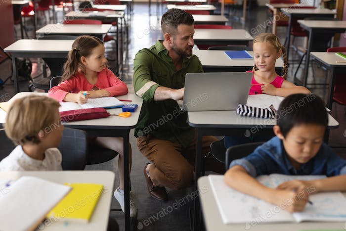 Front view of young school teacher helping girl with study on laptop in classroom