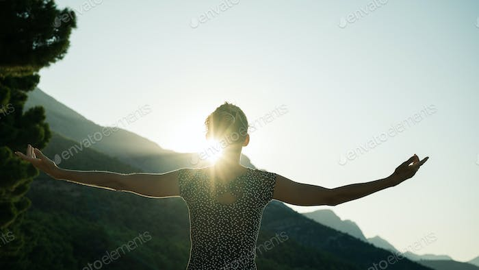 Woman greeting sunrise