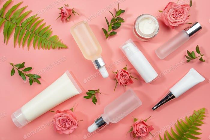 Flache Kosmetikflaschen und -behälter mit Rosen und grünen Farnblättern auf rosa Hintergrund