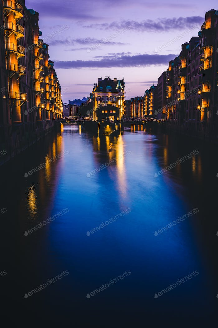 Blue hour in Warehouse District - Speicherstadt with lilac colored sky. Tourism landmark