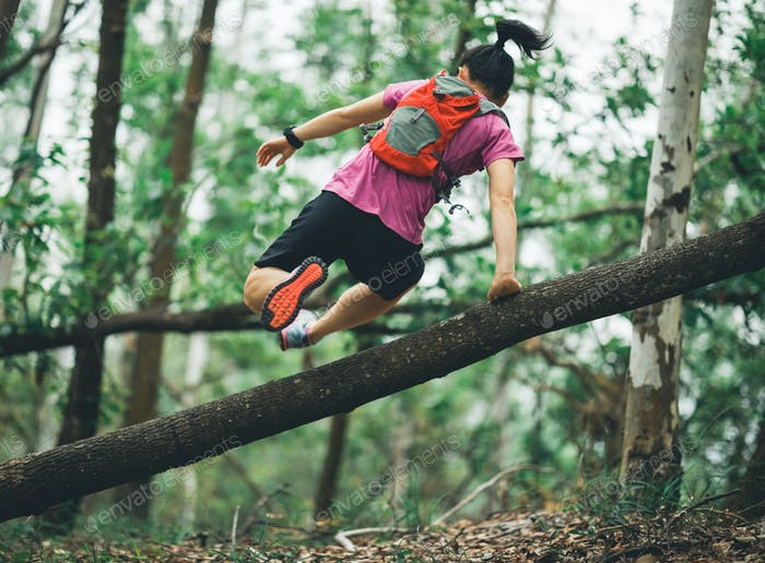 Trail runner  hurdling tree trunk