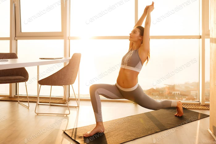 Young lady in sporty top standing and practicing yoga home with beautiful window on background