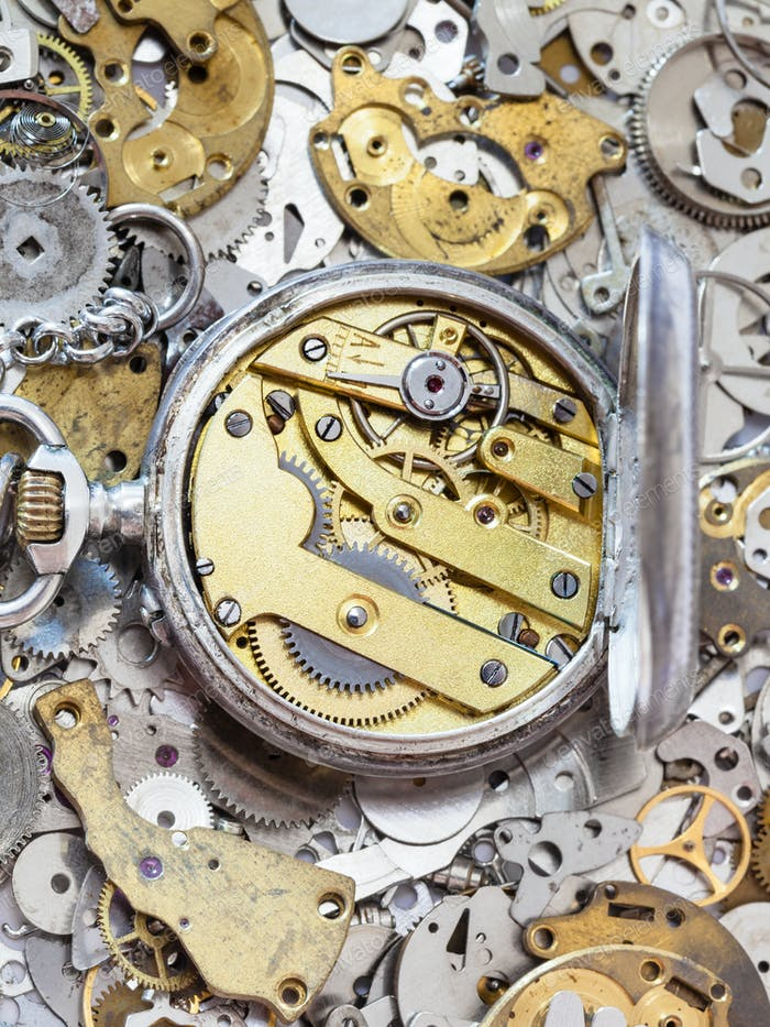 open silver pocket watch on pile of spare parts