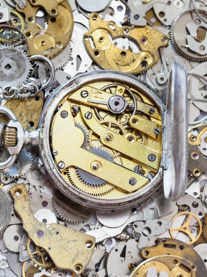 offene silberne Taschenuhr auf Ersatzteilhaufen