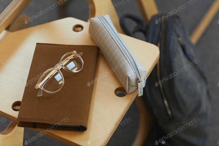 Pencil case and notepad on chair