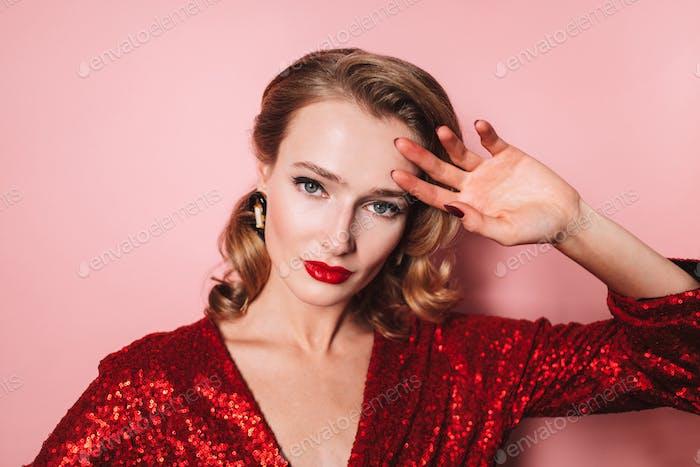 Junge schöne Dame mit welliger Frisur und roten Lippen in hellen