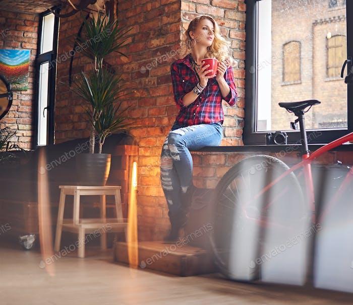 Blond female drinks hot coffee near the window.