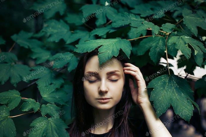 stilvolle Frau unter grünem Blatt, posiert Modellierung