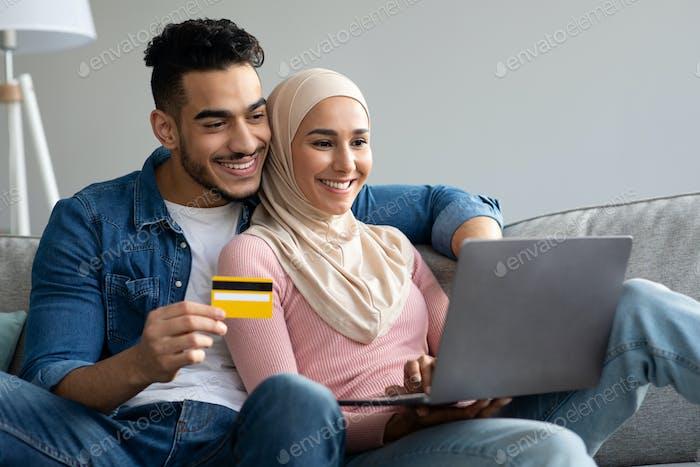 Pareja musulmana sonriente con portátil y tarjeta de crédito