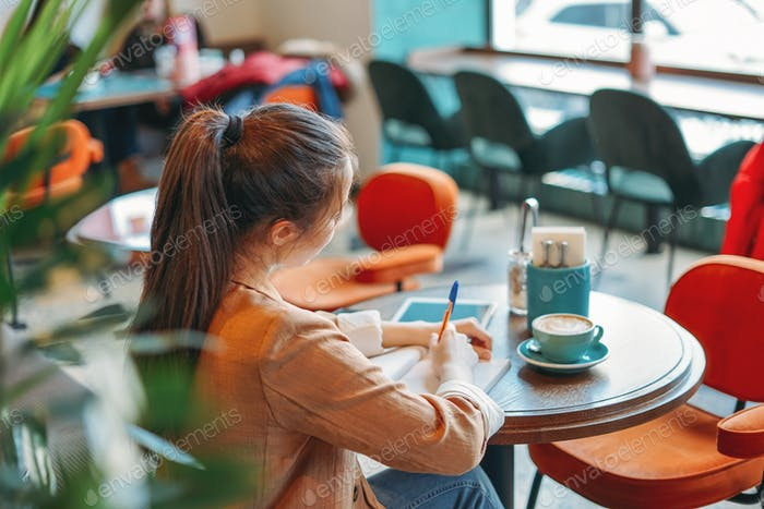 Young brunette asian girl student doing homework in notebook at cafe