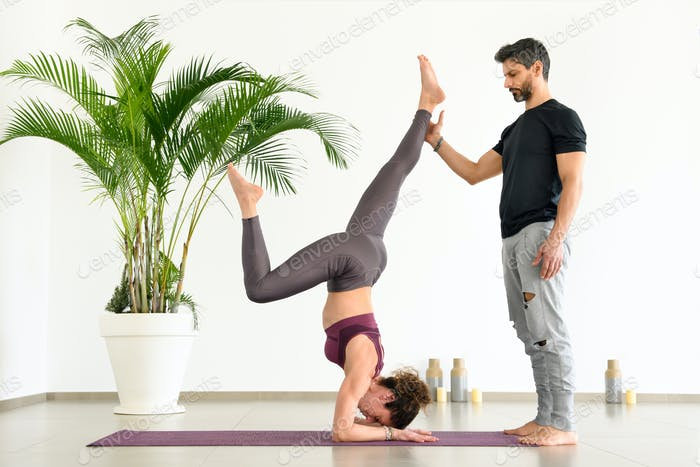 Personal trainer assisting a woman with yoga pose