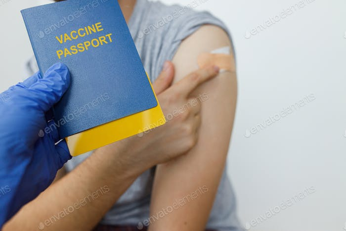 Coronavirus Vaccination passport. Passport with covid-19 vaccine certificate in hand after injection