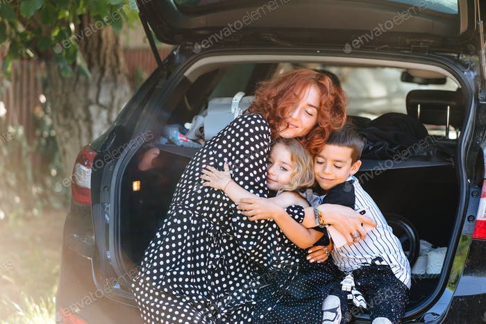 Happy woman sitting with her children in the car