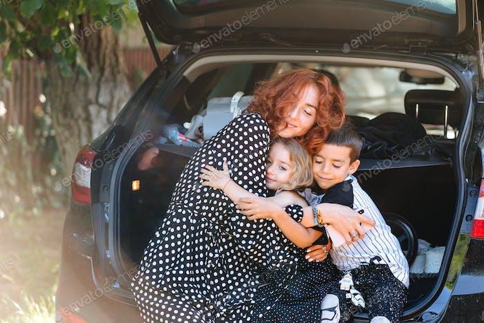Glückliche Frau sitzt mit ihren Kindern im Auto
