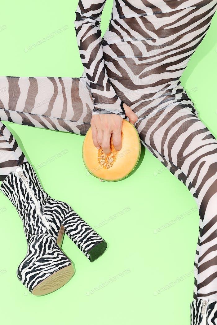 Plaufyl Girl in sexy clothes zebra print with fresh melon between legs. Tropically e