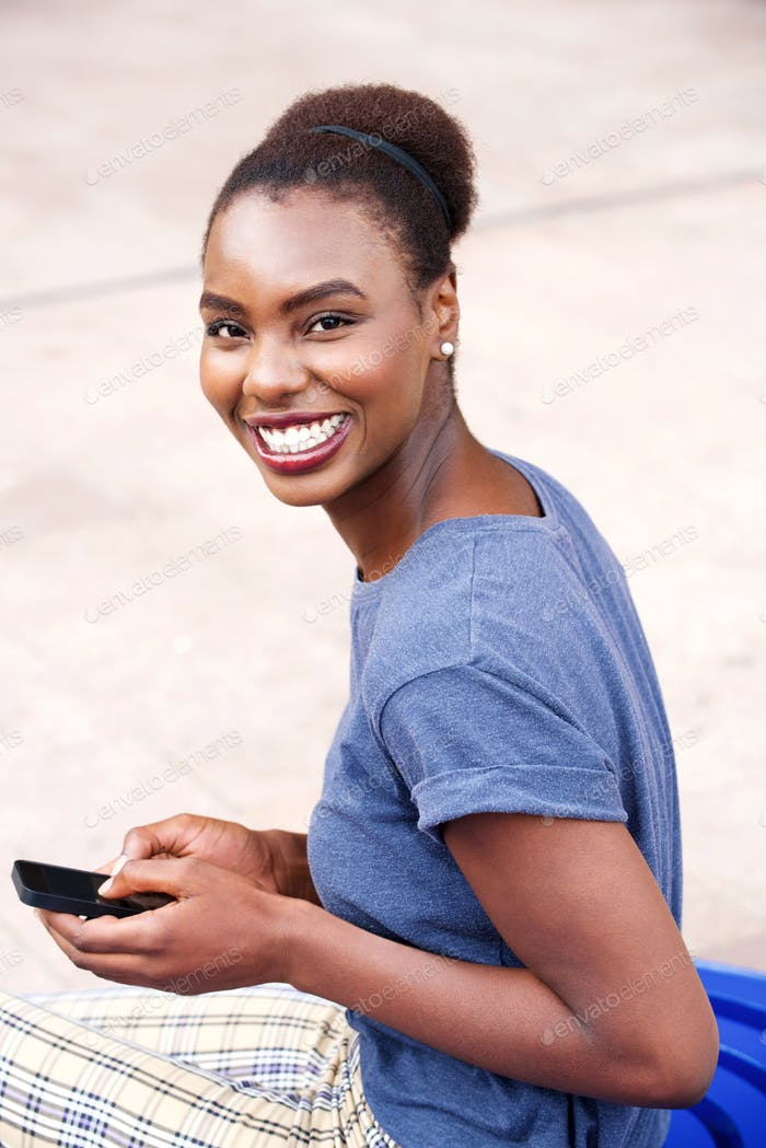 Happy young african woman with mobile phone outdoors