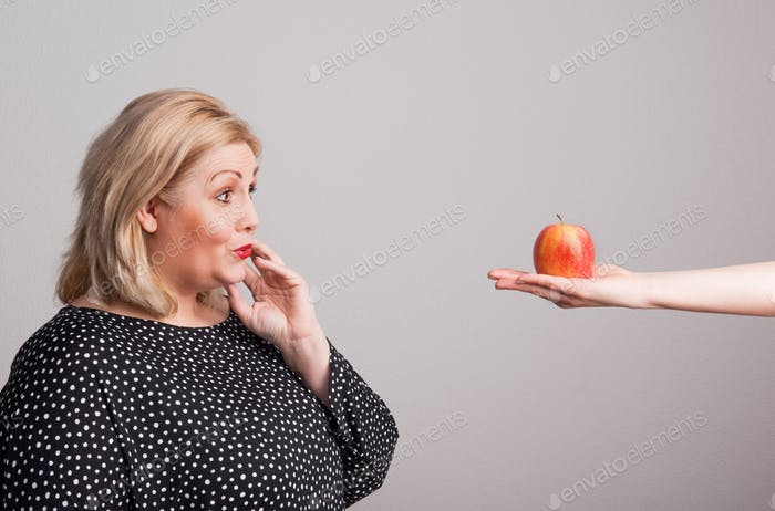 A female hand giving an apple to an attractive overweight woman in studio.