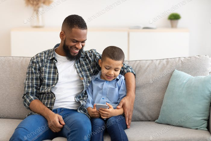 Black Boy And Dad Using Phone Playing Games Online Indoor