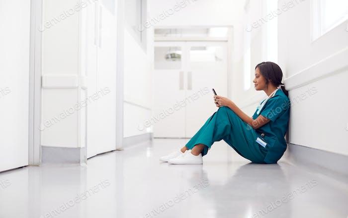 Female Doctor Wearing Scrubs Sitting On Floor In Hospital Corridor Using Mobile Phone