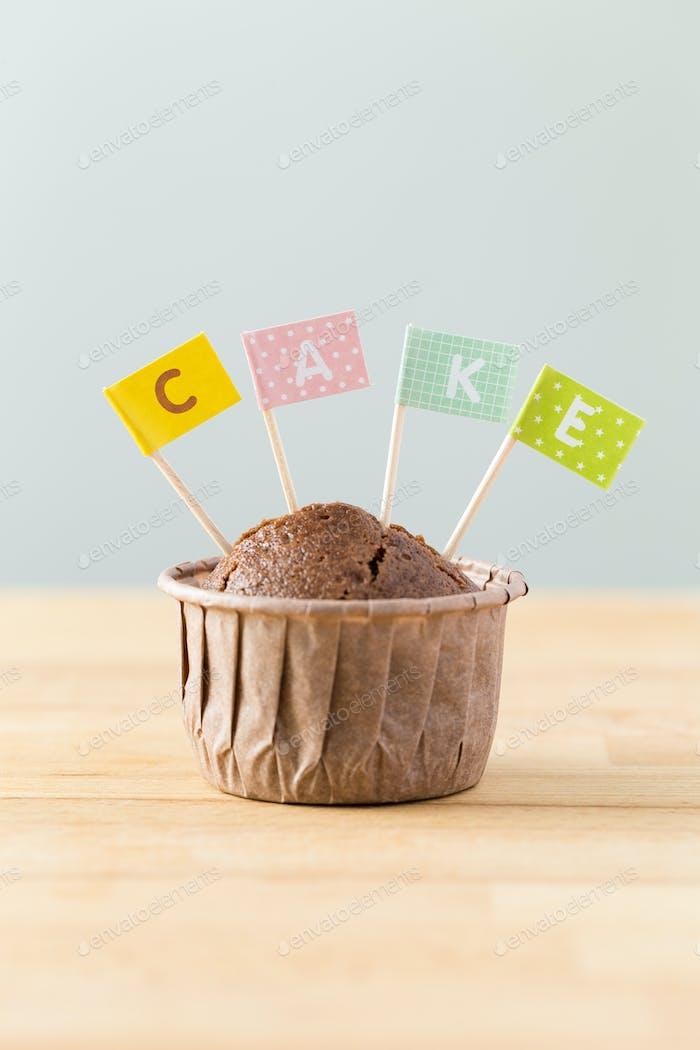 Schokoladenmuffins mit kleiner Flagge eines Wortes Kuchen