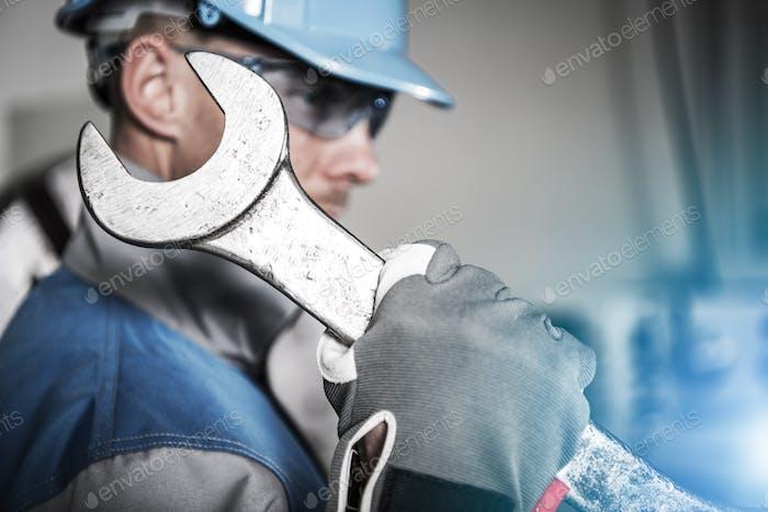 Arbeiter mit riesigem Schraubenschlüssel