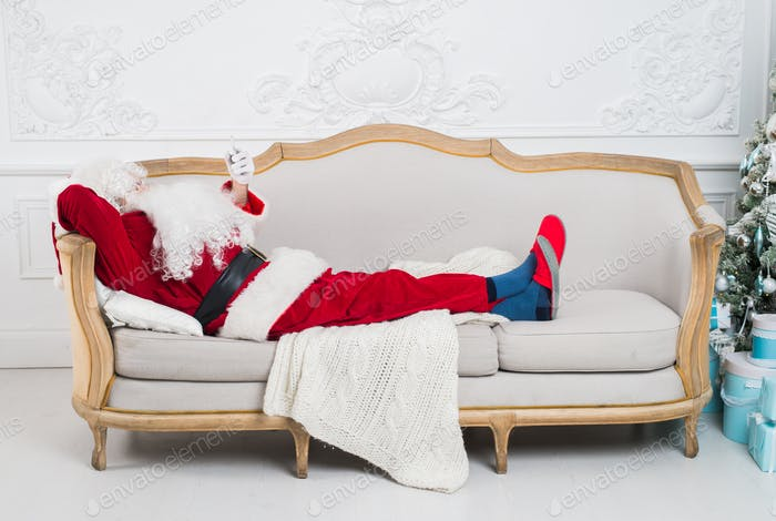 Santa Claus resting on a sofa at home.