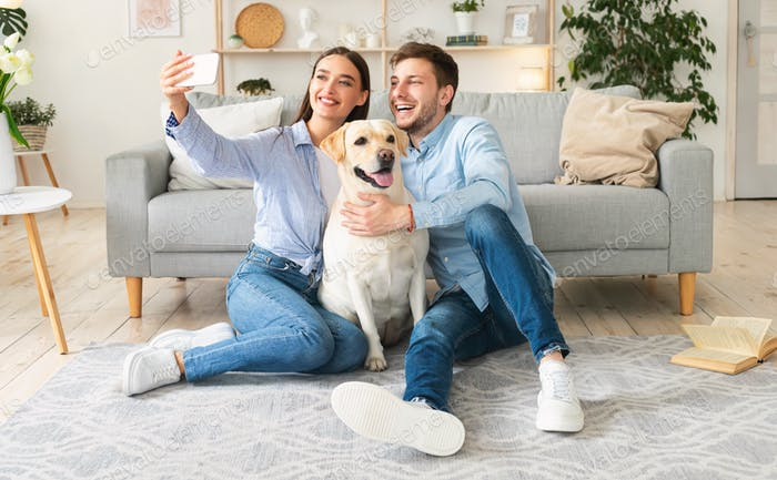 Young couple taking selfportrait with dog at home