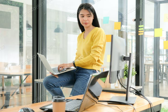 Female programmer are using laptop to place on the leg and create programs for clients.