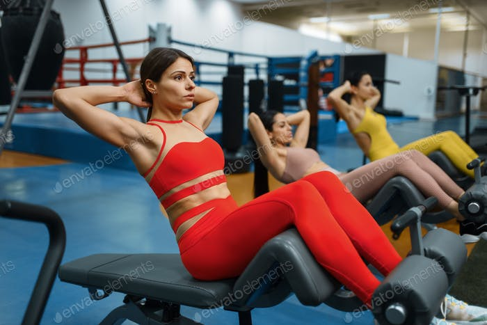Group of women doing abs exercise in gym