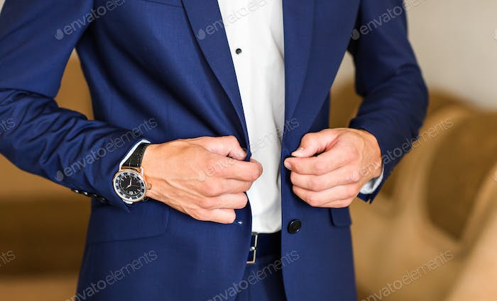 Man buttoning jacket close-up