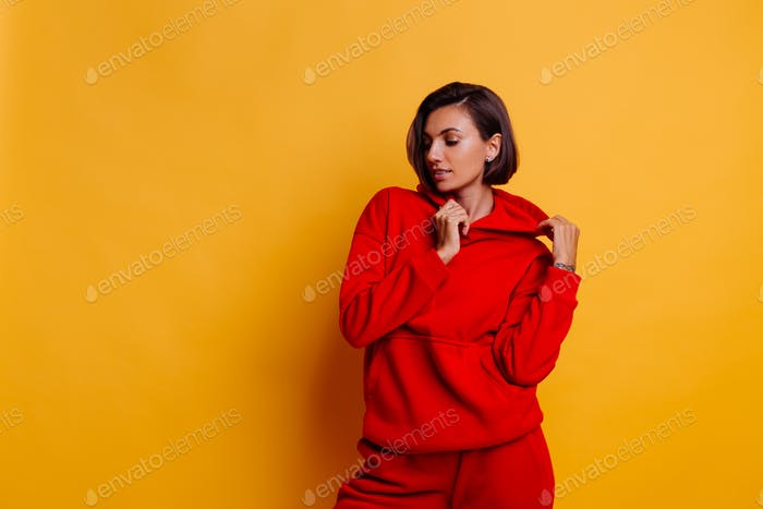 Portrait of happy tanned fit caucasian woman wearing trendy warm red fleece hoodie and pants