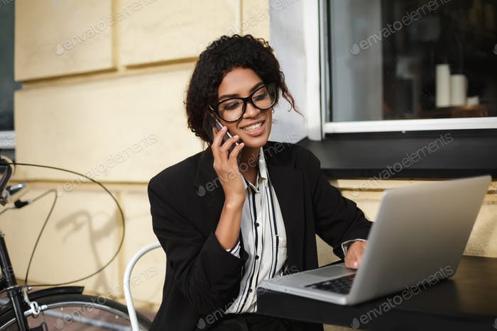 Smiling African American girl in glasses sitting at the table of cafe and working on laptop