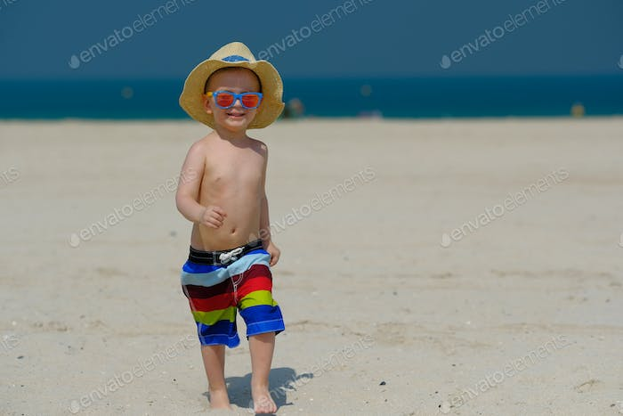 Two year old toddler boy running on beach