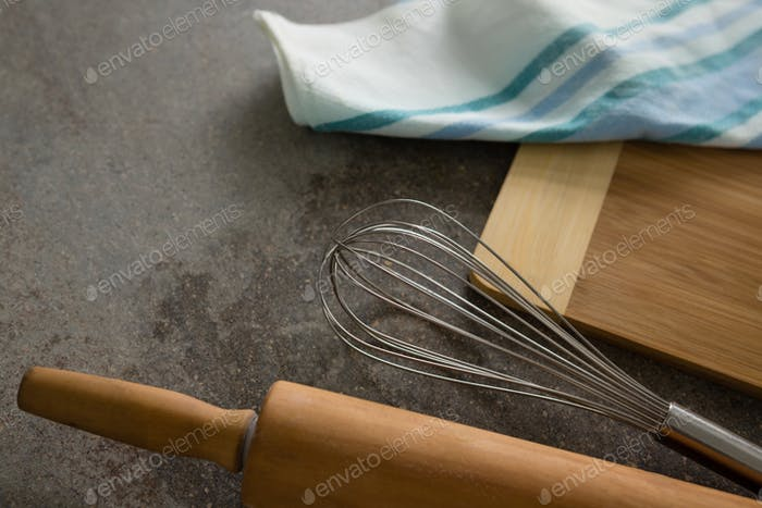 Nudelholz, Whisker, Schneidebrett und Tuch auf Tisch