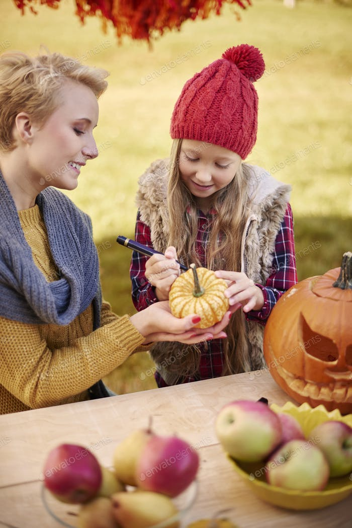 Mother helping daughter in decorating a pumpkin