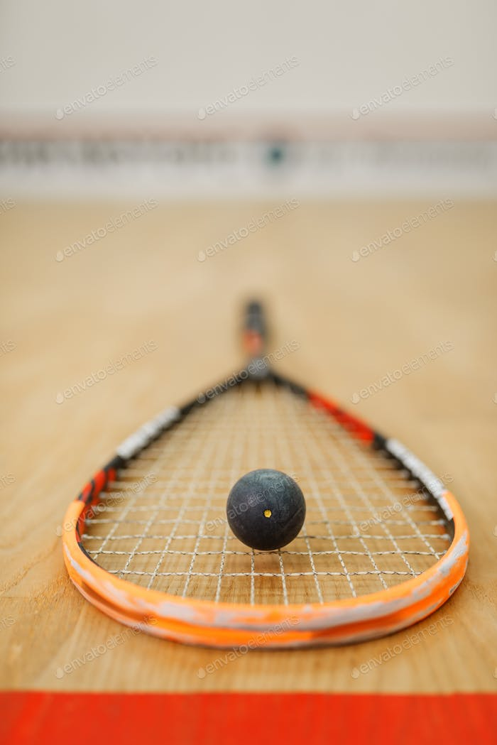 Squash rackets and ball on court floor closeup