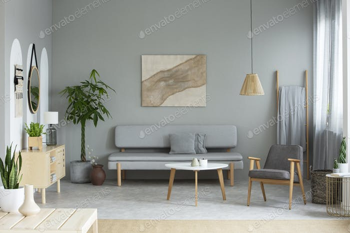 Real photo of grey sitting room interior with modern poster, lou
