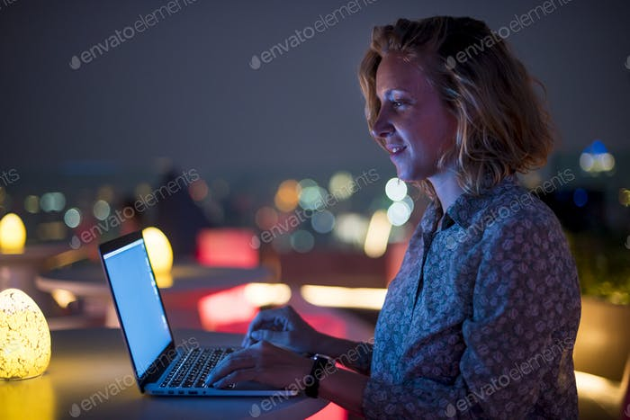 Woman working on a laptop at a rooftop bar