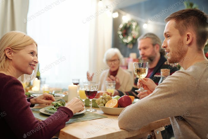 Young man with glass of wine offering toast to his happy mother at dinner