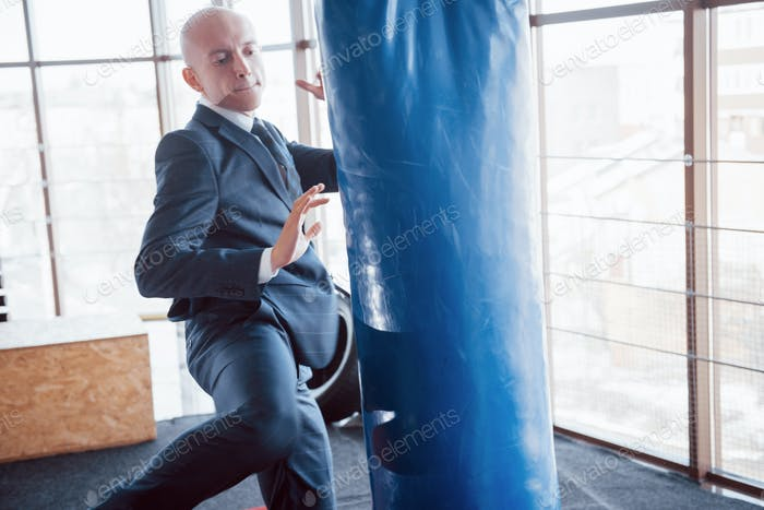 Злой лысый бизнесмен бьет боксерскую груша в тренажерном зале. Концепция управления гневом