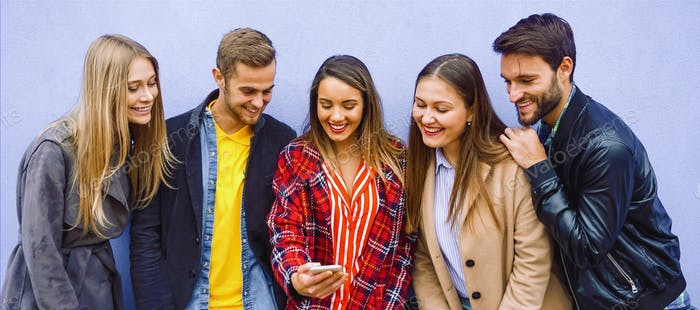 A group of people standing by the wall and takeing a selfie