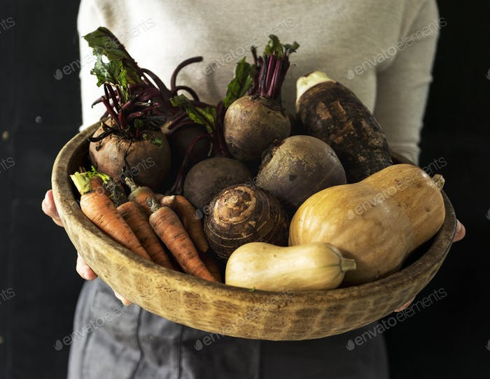 Woman holding various beetroot vegetable in wooden basket