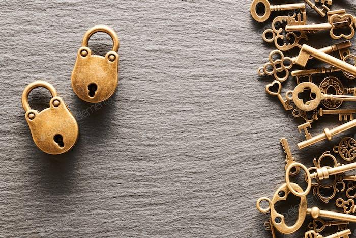 Verschiedene Metallschlüssel und Schlösser auf Schieferhintergrund
