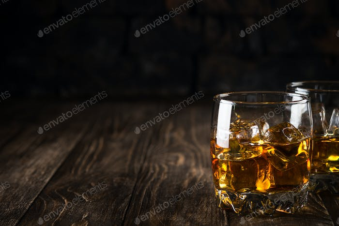 Whiskey in the glasses on dark background