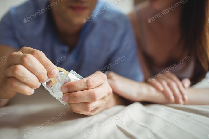 Close-up of couple with a condom on bed